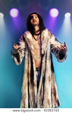 Young rock musician in fur coat making rebellious hand gestures