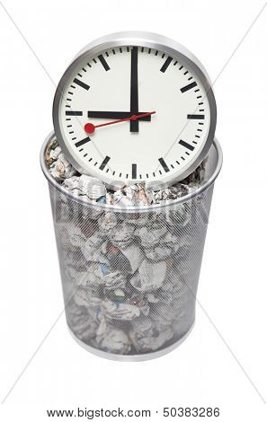 Clock in wastebasket full of crumpled paper over white background