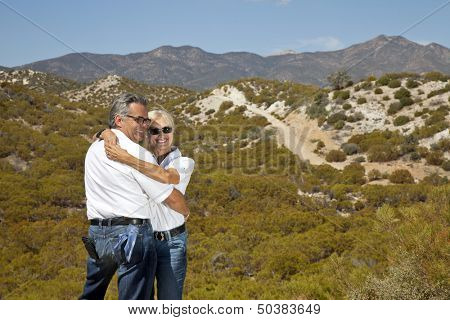 Senior couple hug with desert in background