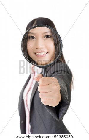 Smiling young asian business woman looking through a magnifying glass. Isolated on the white background.