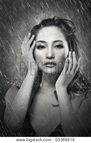 Attractive sexy asian lady in the rain, in bikini. Black and white portrait.