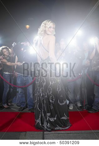 Portrait of young woman in gown posing for paparazzi on the red carpet