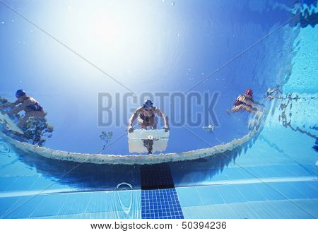 Low angle view of female swimmers ready to dive in pool from starting position