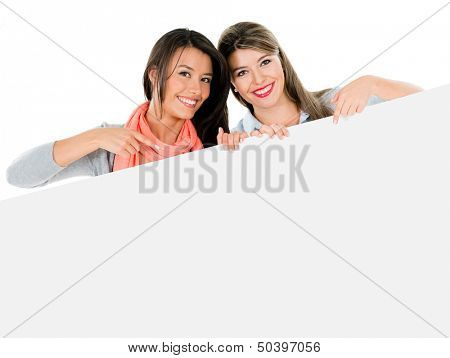 Happy women pointing at a banner - isolated over white background