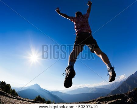 Man jumping in the sunshine against blue sky. Concept: freedom, success, energy, vitality.