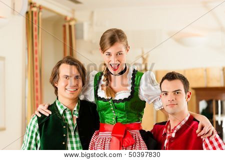 Young couple in traditional Bavarian Tracht in restaurant or pub, they might be the innkeepers with a guest
