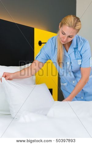Room service - young chambermaid changing the bedding or bedclothes in a hotel room