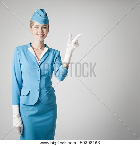 Charming Stewardess Dressed In Blue Uniform Pointing The Finger On Gray Background