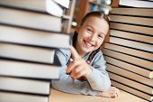 Portrait of cute little girl surrounded by two stacks of books looking at camera