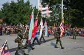 KUALA LUMPUR - AUGUST 31: Women flag-bearers representing the Malaysian Armed Forces march on the ci