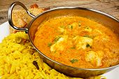 stock photo of curry chicken  - Chicken Korma a popular sweet indian curry dish of coconut and cream sauce served in a dish on a plate with pilaf rice and samosas - JPG