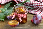 stock photo of jar jelly  - Plum jam in  jar on  wooden table - JPG
