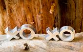 picture of xoxo  - Hugs and kisses symbols xoxo on a rustic wooden background with copy space - JPG