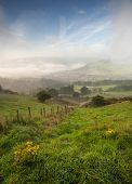 stock photo of swales  - misty yorkshire valley in autumn slowly parting to reveal village below