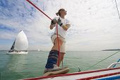 stock photo of sail-boats  - Wide angle shot of beautiful young woman on the deck of a boat holding a rope while behind her a yacht her is a boat she is racing against - JPG