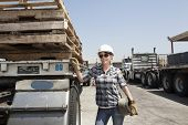 pic of logging truck  - Female industrial worker standing by flatbed truck in timber yard - JPG