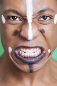 Detail shot of aggressive mixed race man with painted face clenching teeth