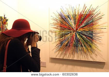 Visitor takes a photo of an artwork