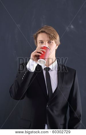 Boy in the jacket with a cup of coffee