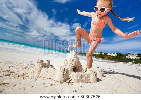 Little girl at tropical beach crushing a sand castle having fun