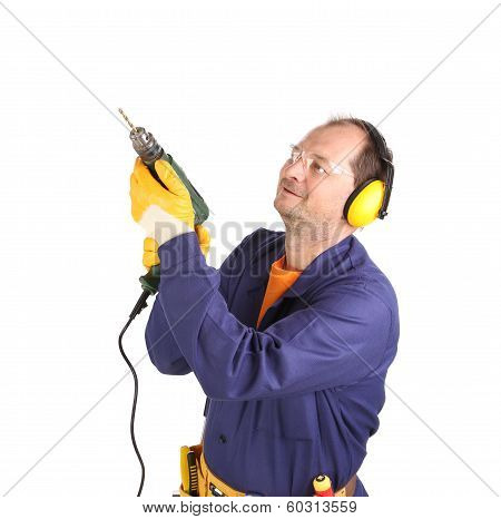 Worker in ear muffs and glasses with drill.