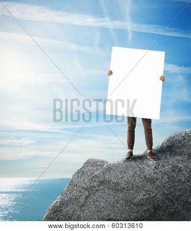 Man standing on a rock with blank poster in his hands