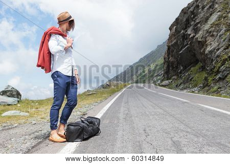 young fashion man standing on the road side and looking up the road for cars while holding his jacket over his shoulder