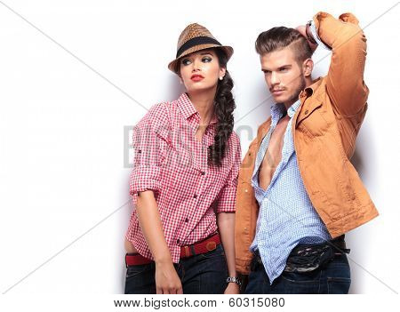man and woman fashion models looking away and posing in studio