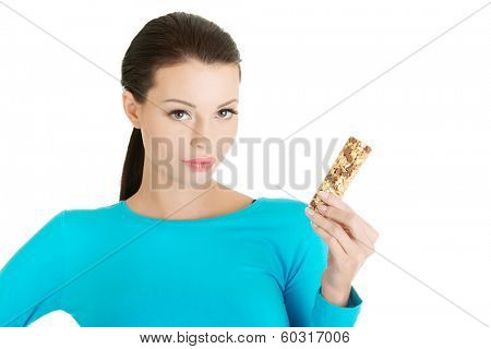 Young woman eating Cereal candy bar, isolated on white