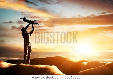 Happy father celebrating his little child by the seaside at sunset, summer time. Birth, new born, fatherhood concepts