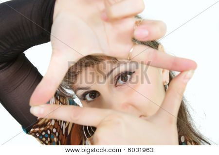 Portrait Of A Woman Looking Through Finger Frame Over White