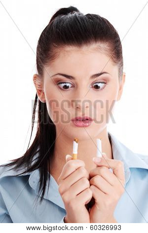 Young woman breaking cigarette over white background