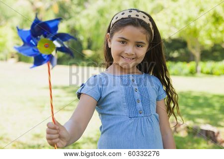 Portrait of cute little girl holding pinwheel at the park