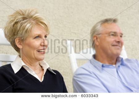 Mature Woman With husband In Background