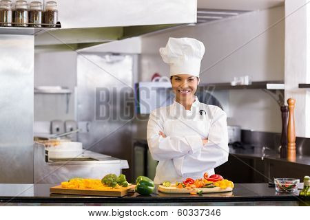 Portrait of a smiling young female chef standing with cut vegetables in the kitchen