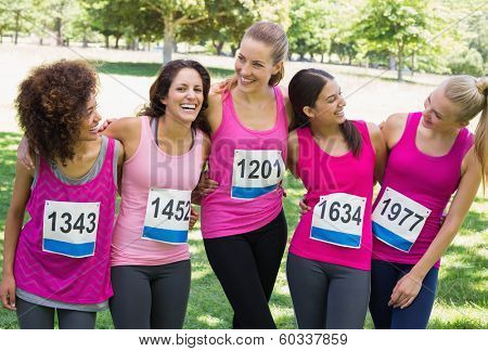 Happy women participating in breast cancer marathon talking at park