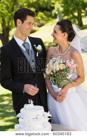 Happy young newlywed couple with wedding cake at the park