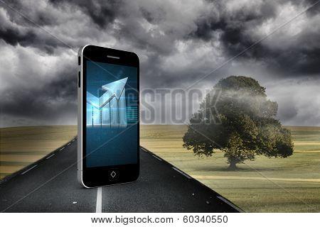 Arrow on smartphone screen against misty green landscape with street
