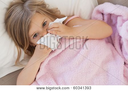 High angle portrait of a cute little girl suffering from cold as she lies in bed