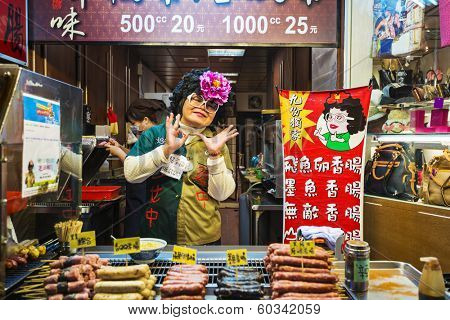 JIUFEN, TAIWAN - JANUARY 17, 2013: A food vendor poses with her goods. The town is a renowned tourist attraction.