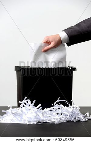 Business man shredding a document