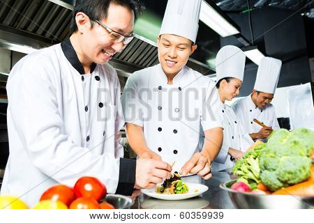 Asian Indonesian chef along with other cooks in restaurant or hotel commercial kitchen cooking, finishing dish or plate