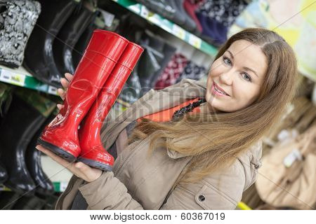 Smiling Customemr Holding Red Watertights When Buying In Shop
