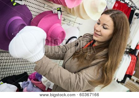 Woman Buying Winter Hat In Shopping Center