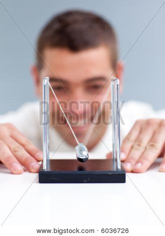 Businessman Looking At Pendulum Balls