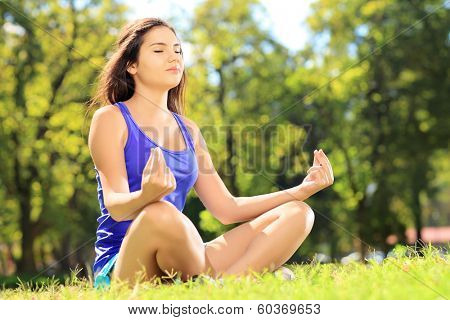 Young female athlete in sportswear meditating seated on a green grass in a park