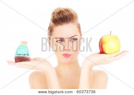 A picture of a woman trying to make a decision between cupcake and apple over white background