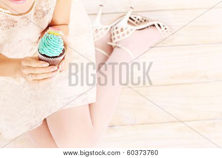 A picture of a woman holding a delicious cupcake over wooden background