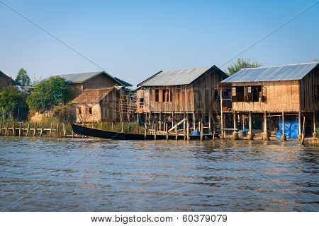 Traditional Stilts House And Long Boats In Water Under Blue Sky