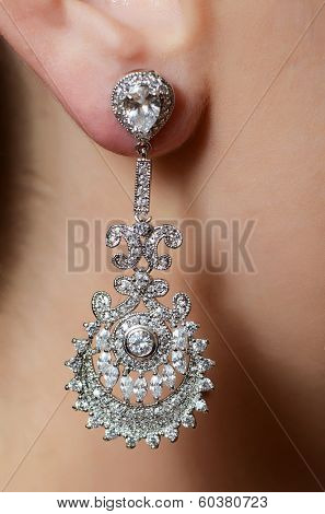 Female ear in jewelry earrings close up